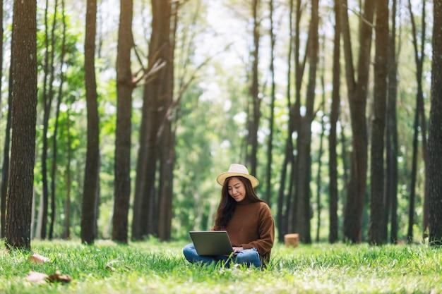 Kobieta pracuje i pisze na klawiaturze laptopa siedząc w parku