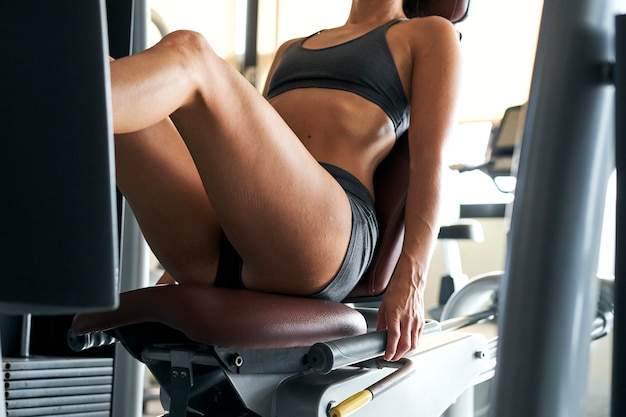 Kobieta pracuje jej quady w prasie maszynowej na siłowni