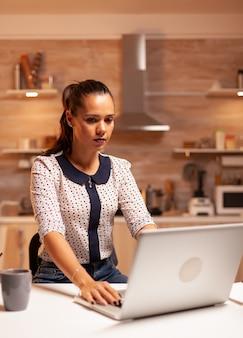 Kobieta pracuje na komputerze w terminie późno w nocy. pracownik korzystający z nowoczesnych technologii o północy wykonujący nadgodziny w pracy, firmie, zajęty, karierze, sieci, stylu życia, bezprzewodowo.