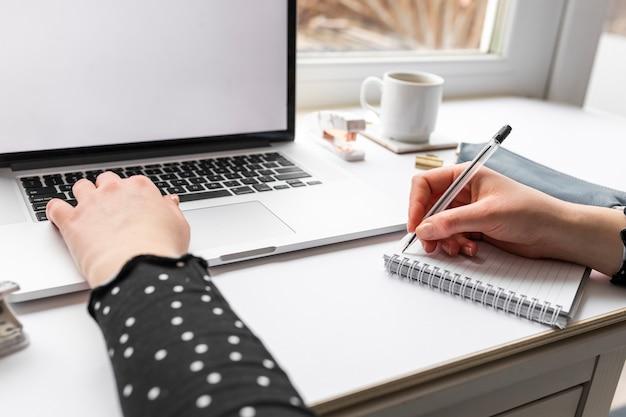 Kobieta pracuje na laptopie i daje zadanie notatkom
