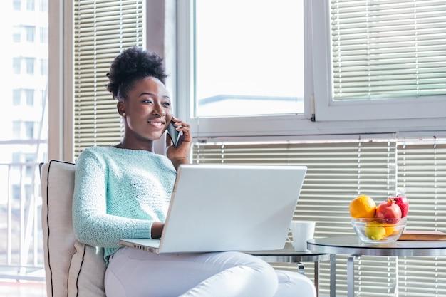Kobieta pracuje na laptopie i rozmawia przez telefon