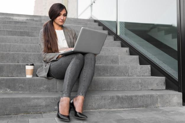 Kobieta pracuje na laptopie mając kawę na schodach