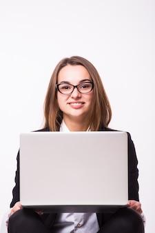 Kobieta pracuje na laptopie na białym tle na białej ścianie