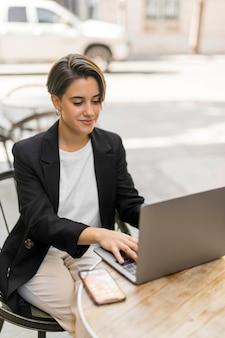 Kobieta pracuje na laptopie na zewnątrz