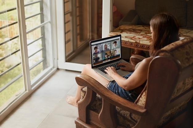 Kobieta pracuje na laptopie online w domu. kobieta za pomocą laptopa do wyszukiwania w internecie, przeglądania informacji. nauka na odległość. wolny strzelec