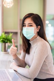 Kobieta pracuje na laptopie podczas noszenia maski medycznej i daje kciuki do góry