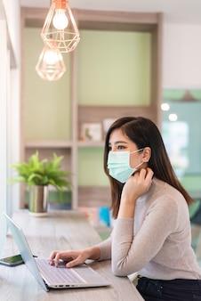 Kobieta pracuje na laptopie podczas noszenia maski medycznej