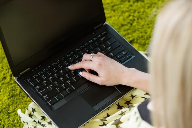 Kobieta pracuje na laptopie. pusty ekran. pisanie na klawiaturze