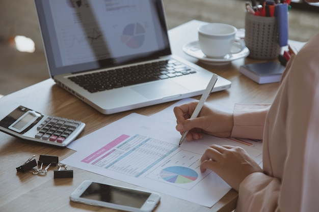 Kobieta pracuje na laptopie w jej stacji roboczej. czarny pusty ekran smartfona, roślina doniczkowa, ołówek, notatki, słuchawki na drewnianym biurku. ścieśniać
