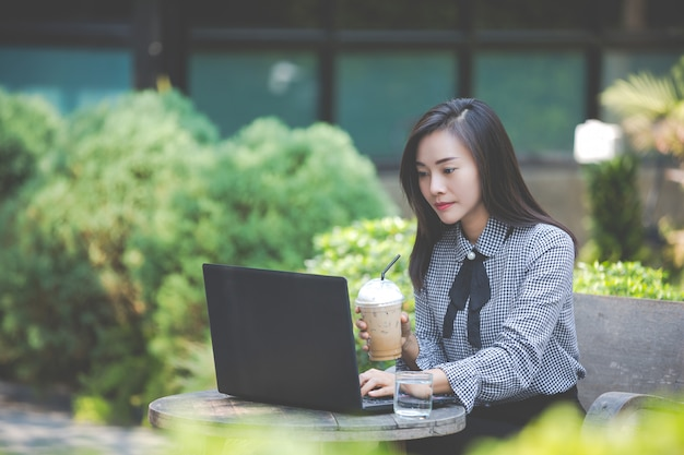 Kobieta pracuje na laptopie w kawiarni i pije kawę