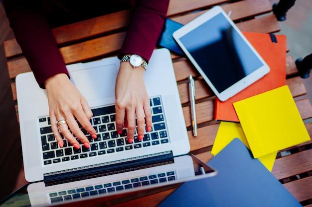 Kobieta pracuje na laptopie w kawiarni. kobiet ręki pisać na maszynie na klawiaturze. nowożytny notatnik, pastylka, notatnik na drewnianym stole.