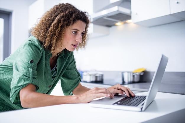 Kobieta pracuje na laptopie w kuchni