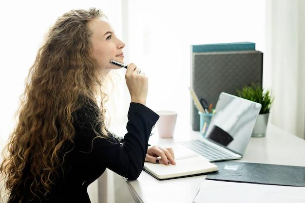 Kobieta pracuje na laptopie w miejscu pracy