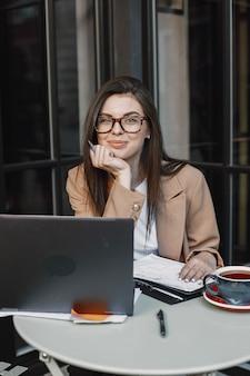 Kobieta pracuje na laptopie w ulicznej kawiarni. noszenie stylowych eleganckich ubrań - kurtki, okularów