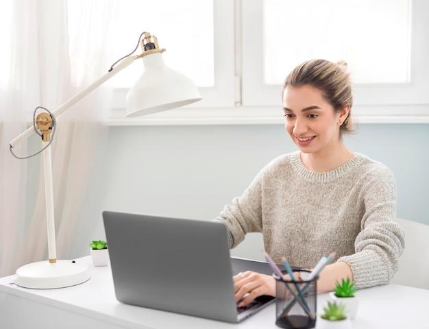 Kobieta pracuje na laptopie z domu