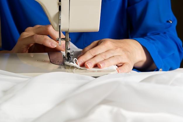 Kobieta pracuje na maszynie do szycia. krawcowa szyje białe zasłony, widok z bliska.