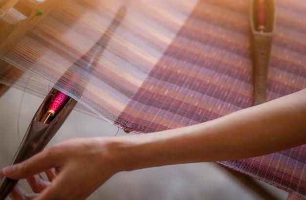 Kobieta pracuje na maszynie do tkania tkaniny ręcznie tkane. tkactwo tekstylne. tkanie przy użyciu tradycyjnego krosna ręcznego do tkania na pasmach bawełny. tekstylia lub tkaniny.