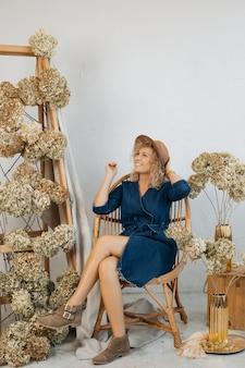Kobieta pracuje nad piękną dekoracją kwiatową do pokoju, z suszonych kwiatów, blondynka kwiaciarnia jest zadowolona z wykonanej pracy, uśmiecha się i odwraca wzrok