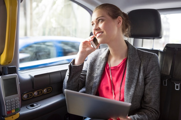 Kobieta pracuje podczas jazdy taksówką
