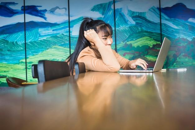 Kobieta pracuje przy laptopem przy stołem