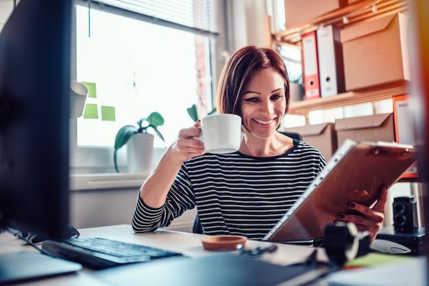 Kobieta pracuje w biurze i pije kawę