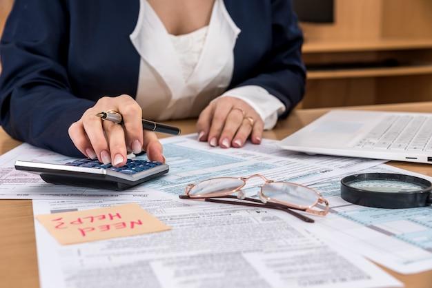 Kobieta pracuje w biurze - kalkulator dochodów z formularza zwrotu podatku