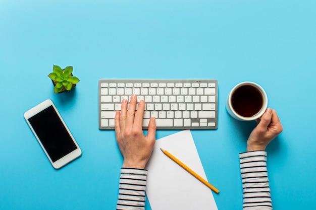 Kobieta pracuje w biurze na niebiesko. koncepcja obszaru roboczego, praca przy komputerze, niezależny