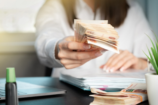 Kobieta pracuje w biurze. przeliczanie banknotów. ręka daje pieniądze z bliska.
