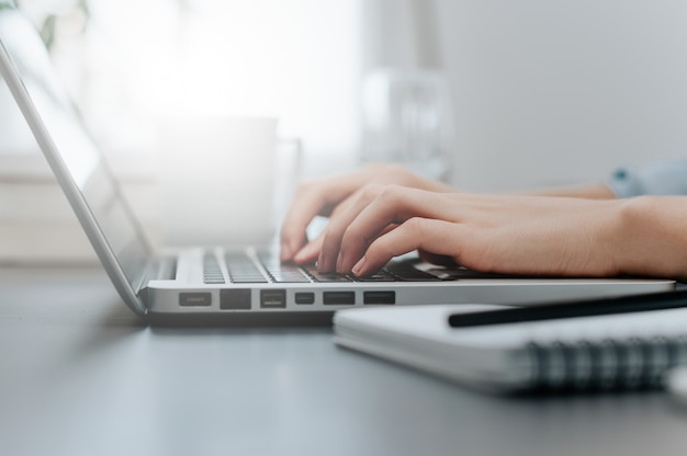 Kobieta pracuje w domowym biurze ręka na klawiaturze z bliska