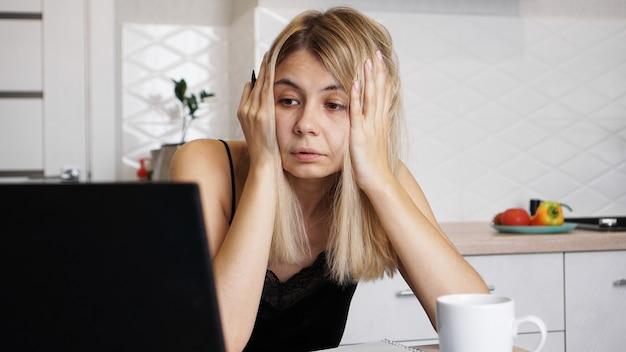 Kobieta pracuje w domu lub uczy w domu ucznia, używając swojego laptopa. kobieta trzymająca się za głowę i zmartwiona problemem