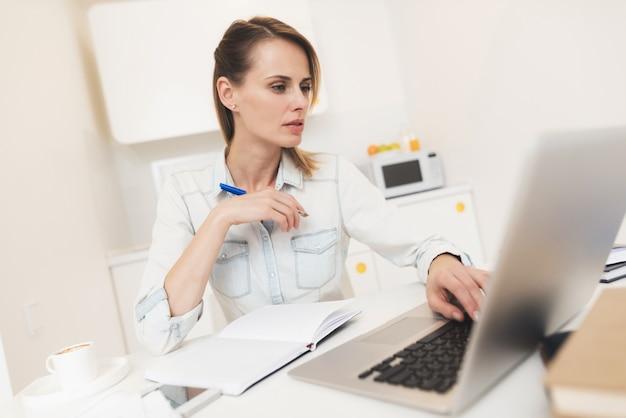 Kobieta pracuje w domu. pracuje na laptopie.