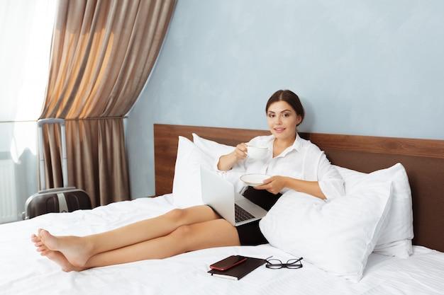 Kobieta pracuje w pokoju hotelowym