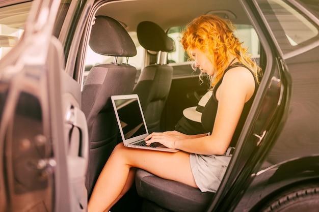 Kobieta pracuje w tylnym siedzeniu samochodu