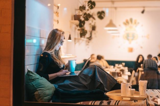 Kobieta pracuje wieczorem w kawiarni
