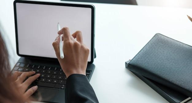 Kobieta pracuje z rysikiem na cyfrowym tablecie z laptopem w nowoczesnym biurze.