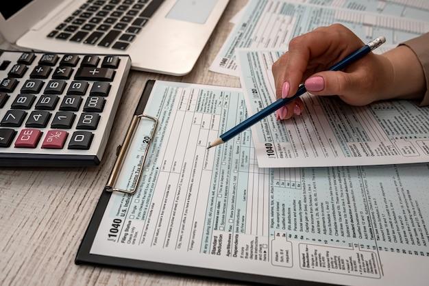 Kobieta pracuje z usa formularz podatkowy 1040 i laptop kalkulator w biurze. koncepcja rachunkowości