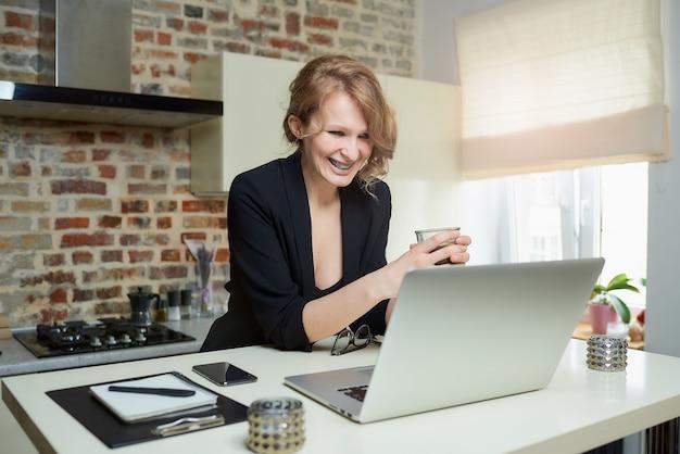 Kobieta pracuje zdalnie na laptopie. roześmiana dziewczyna z aparatami ortodontycznymi trzyma filiżankę kawy, słuchając raportu kolegi z konferencji online w domu.