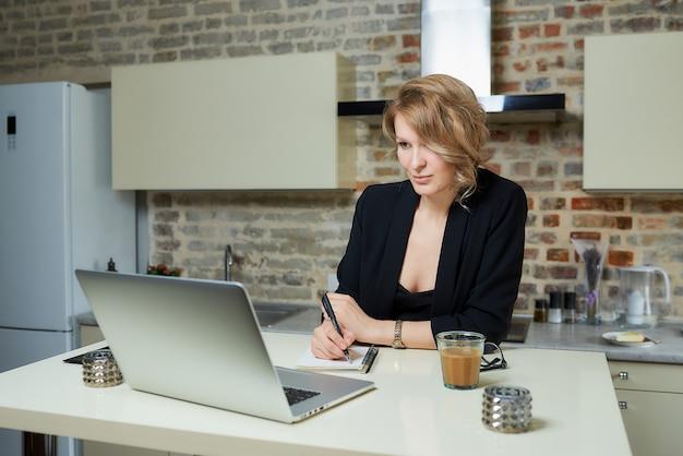 Kobieta pracuje zdalnie na laptopie w kuchni. dziewczyna robi notatki do notesu podczas raportu kolegi z wideokonferencji w domu.