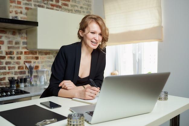 Kobieta pracuje zdalnie na laptopie w kuchni. roześmiana dziewczyna robi notatki do notesu podczas raportu kolegi z wideokonferencji w domu.