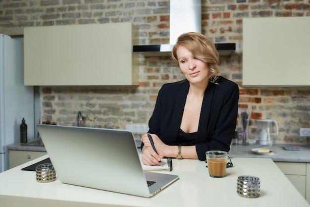 Kobieta pracuje zdalnie na laptopie w kuchni. szczęśliwa dziewczyna robi notatki do notesu podczas raportu kolegi z wideokonferencji w domu. nauczyciel przygotowuje się do wykładu online.