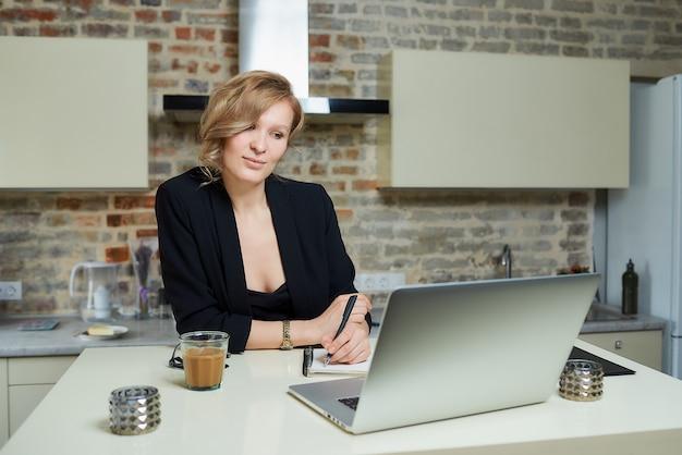 Kobieta pracuje zdalnie na laptopie w kuchni. szczęśliwa dziewczyna robi notatki do notesu podczas raportu kolegi z wideokonferencji w domu ..