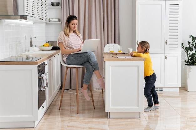 Kobieta pracuje zdalnie z dzieckiem pełne ujęcie