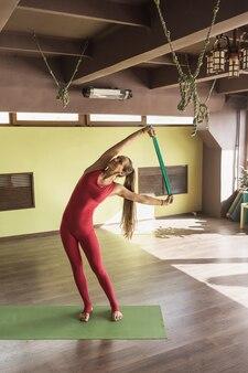 Kobieta praktykująca terapię jogą wykonuje boczne skłony za pomocą paska