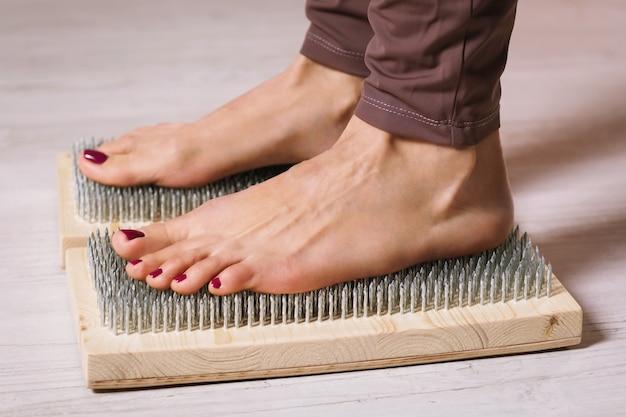 Kobieta praktykująca terapię jogi stoi na desce z gwoździami