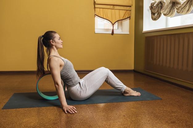 Kobieta praktykująca zdrowy tryb życia wykonująca masaż mięśniowo-powięziowy mięśni pleców z wykorzystaniem koła jogi na macie