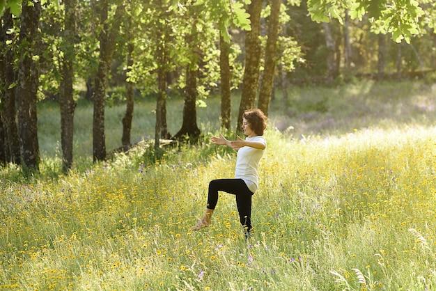 Kobieta praktykuje jogę na łące kwiatów