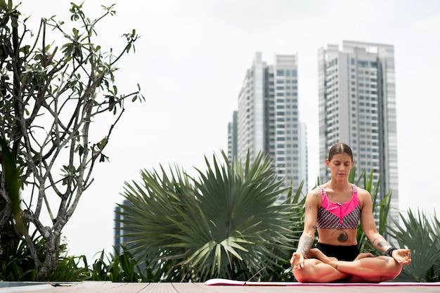 Kobieta praktykuje jogę na macie na zewnątrz obok basenu