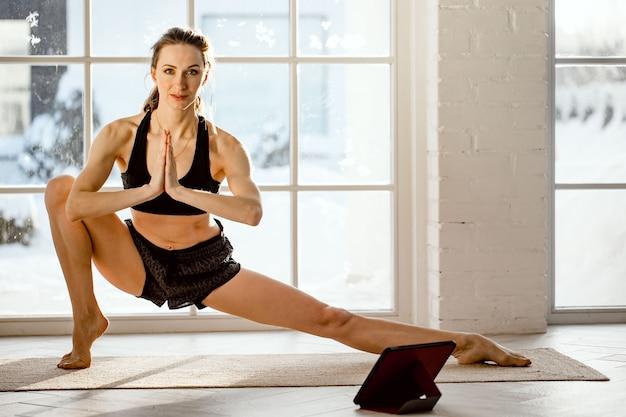 Kobieta praktykuje jogę online z tabletem