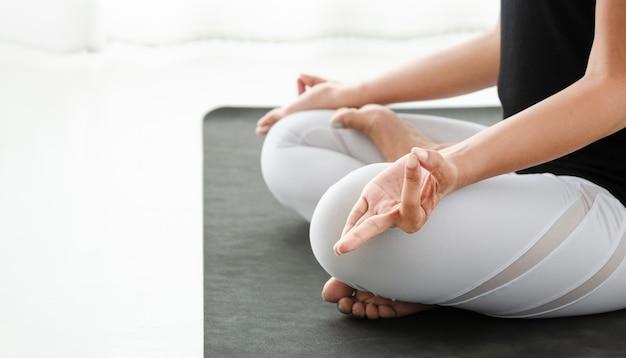 Kobieta praktykuje jogę w pozycji lotosu lub padmasana z mudrą. siedząca pozycja medytacyjna ze skrzyżowanymi nogami w białej sypialni po przebudzeniu się rano. pojęcie ćwiczeń, relaksu i opieki zdrowotnej.