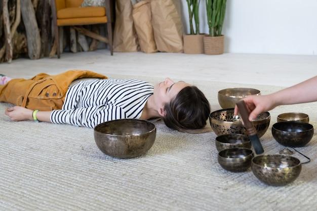 Kobieta praktykuje terapię dźwiękiem śpiewających mis tybetańskich w celu wyleczenia lęku i złagodzenia stresu w domu